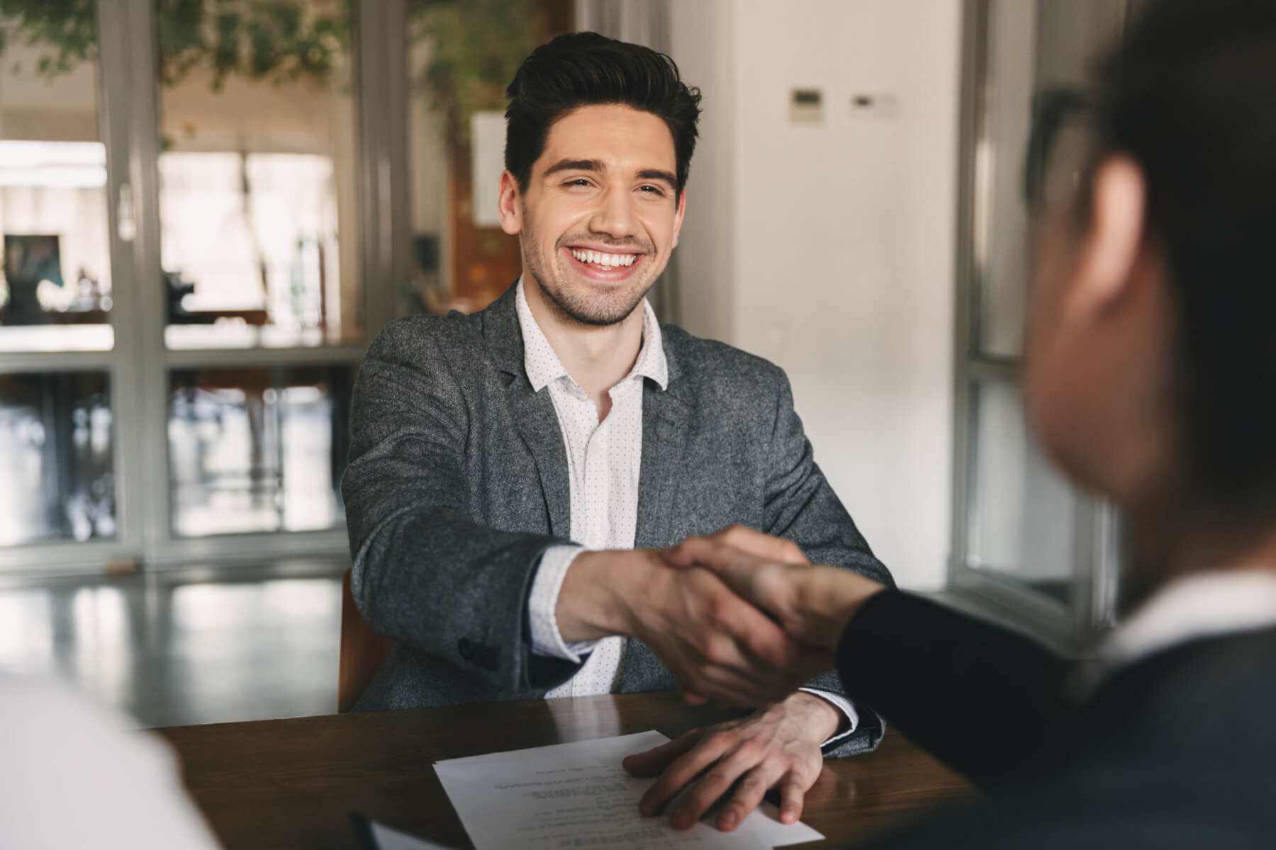 Business, career and placement concept – happy caucasian man 30s rejoicing and shaking hands with employee, when was recruited during interview in office